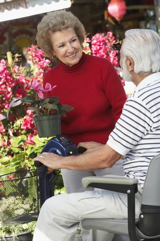 Senior woman showing plant to man on motor scooter at botanical garden