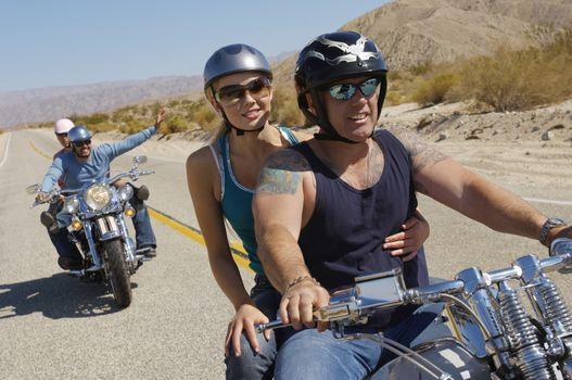 Four friends enjoying bike ride on desert road
