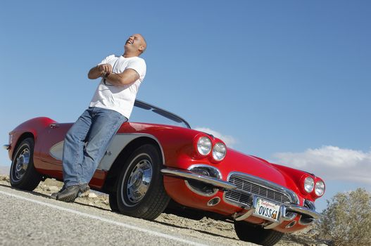 Man laughing while standing by classic car on desert road
