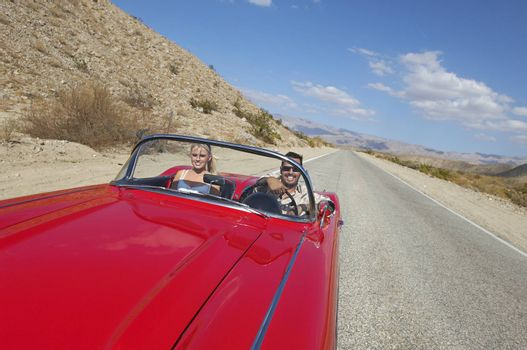 Happy multiethnic couple in red classic car on desert road