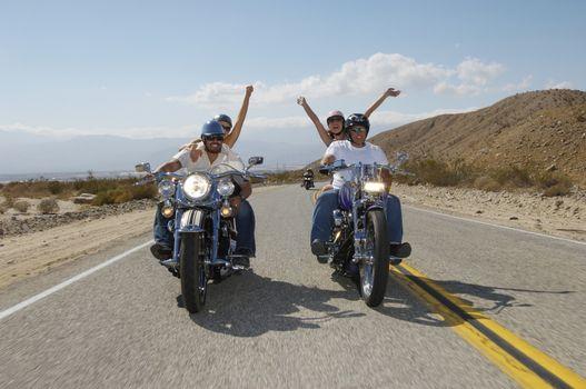 Couples enjoying bike ride on desert road