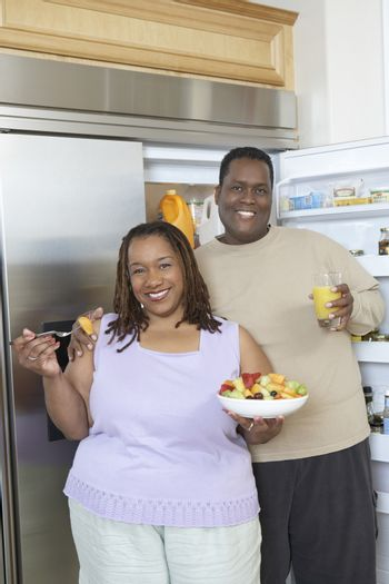 Couple with food and drink by open fridge