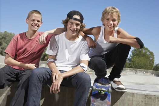 Three teenage boys (16-17) with skateboards at skate park portrait