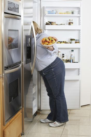 Woman looking into fridge side view