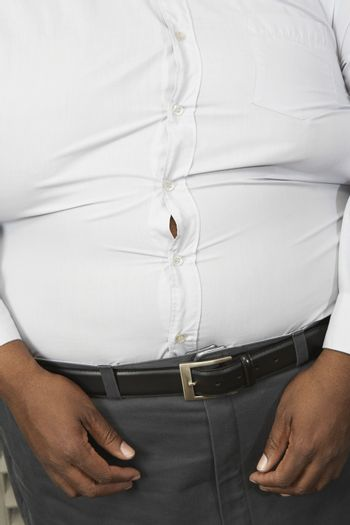 Midsection of an obese man wearing tight formal white shirt
