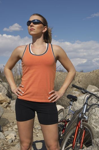Female cyclist with hands on hips in mountains