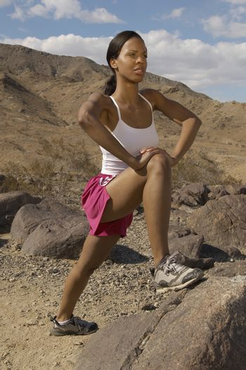 Mixed race female jogger stretching on rock