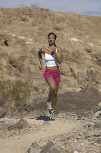 Mixed race young woman jogging in mountains