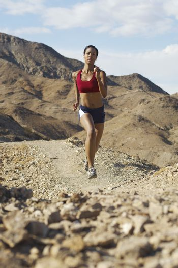 Mixed race woman jogging in mountains