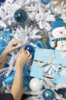 Closeup of female hands decorating Christmas tree