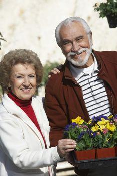 Portrait of happy Hispanic couple with flower pots at botanical garden