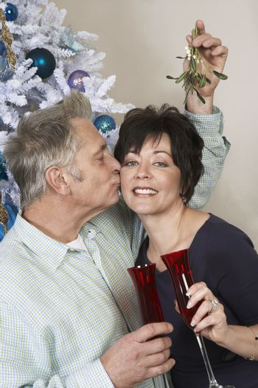Senior man kissing woman under mistletoe in front in Christmas tree