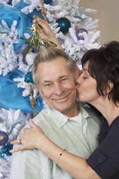 Woman kissing Caucasian man under mistletoe in front in Christmas tree