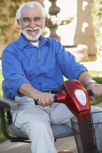Portrait of a cheerful senior man on motor scooter