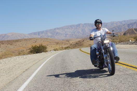 Man riding motorcycle on desert road