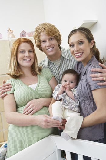 Portrait of happy expectant couple with woman and baby standing by cradle