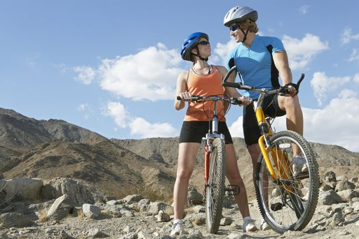 Young couple on bicycles in mountains