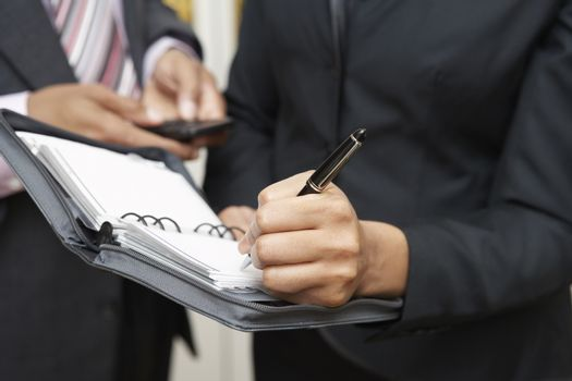 Midsection of businesswoman writing in diary