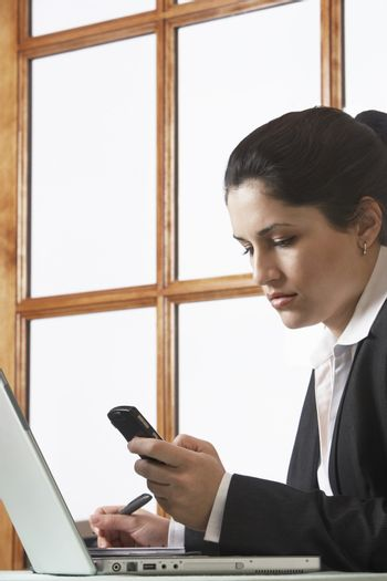 Young businesswoman text messaging in office