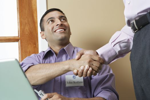 Businessman welcoming colleague with a hand shake in office