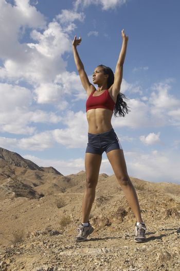 Mixed race female jogger stretching her arms in mountains