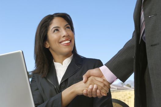 Happy African American businesswoman shaking hand with colleague