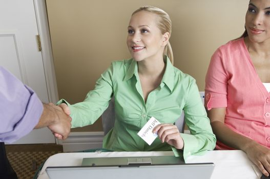 Receptionist with name tag shaking hands with a man