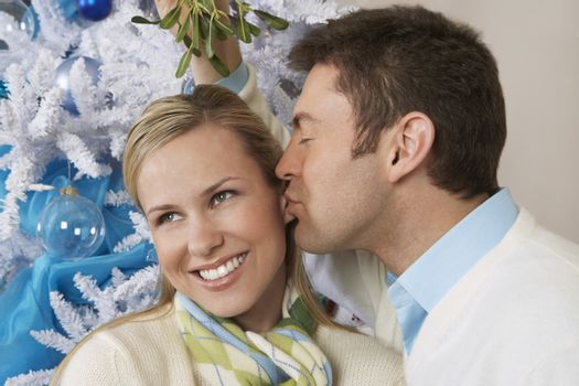 Young man kissing happy woman under mistletoe in front of Christmas tree