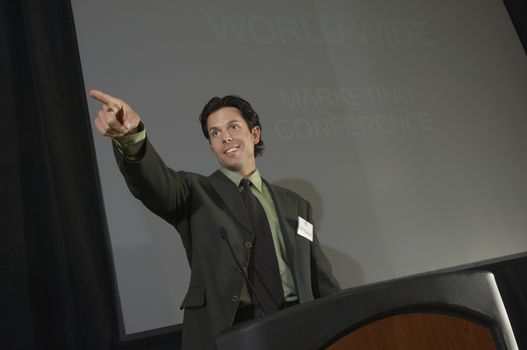 Mid adult man pointing during presentation at conference