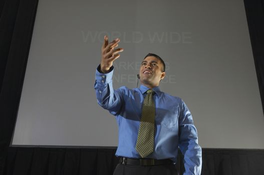 Businessman speaking against projector screen at conference