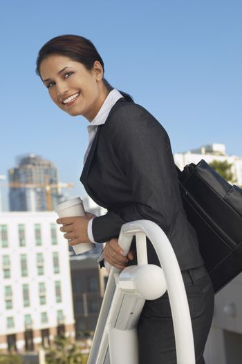 Portrait of a beautiful businesswoman holding disposable coffee cup at railing