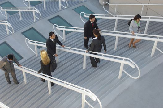 Business people moving up and down stairs elevated view