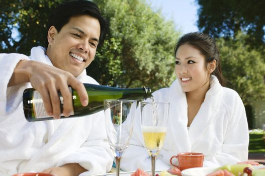 Chinese Couple Wearing Bathrobes Drinking Champagne