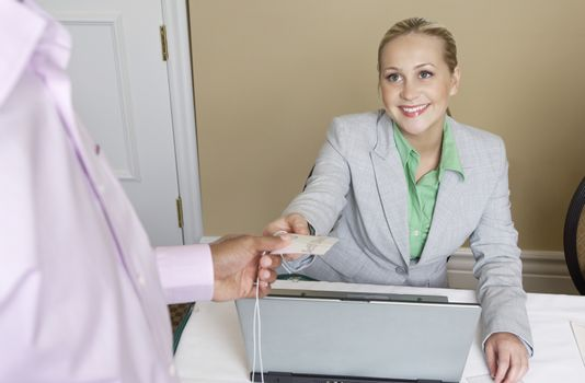 Happy Caucasian receptionist handing name tag to a man