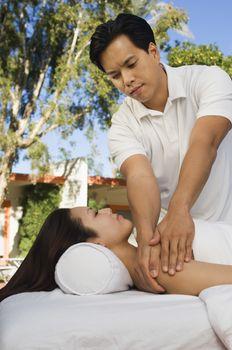 Masseuse massaging young woman at health spa