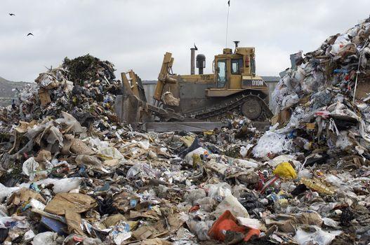 Excavator moving garbage at dumping ground