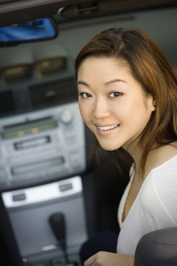 Portrait of a beautiful young Korean woman smiling in car