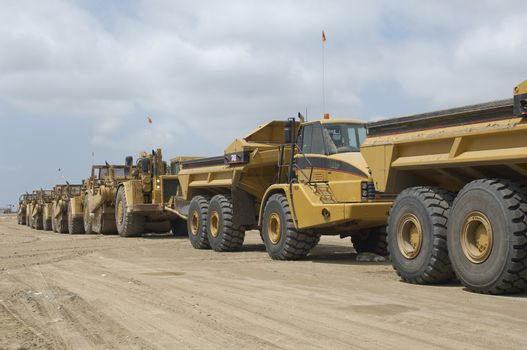 Dump trucks parked in a row at landfill site