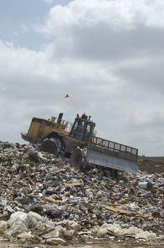 Excavator moving trash at a landfill