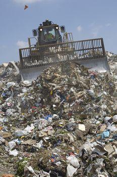 Digger moving trash in a landfill