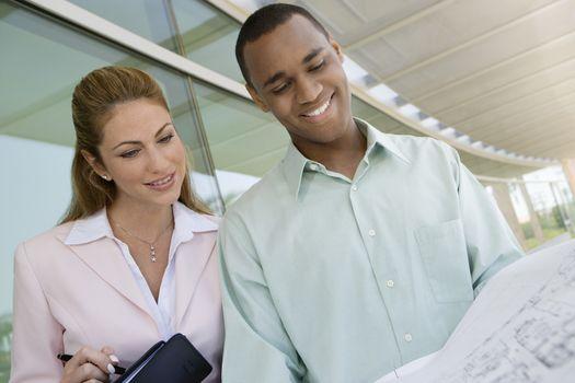 Happy multiethnic businesspeople looking at blueprint