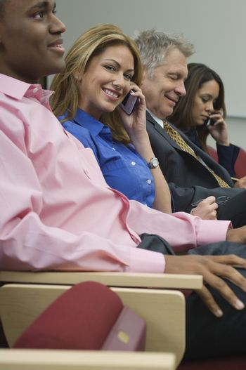 Portrait of businesswoman on call with colleagues in a row during seminar
