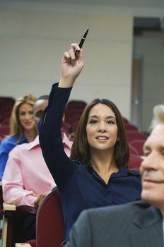 Female executive raising hand during a business seminar amid colleagues