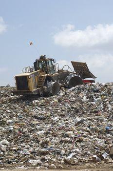 An Excavator moving garbage at dumping ground