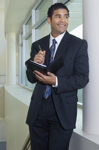 Happy African American businessman holding dairy while leaning by window