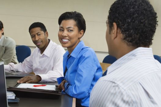 Multi ethnic business people sitting in classroom