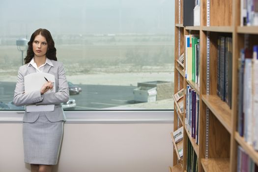 Thoughtful female executive in library