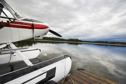 Sea plane tied up to wooden dock at lake