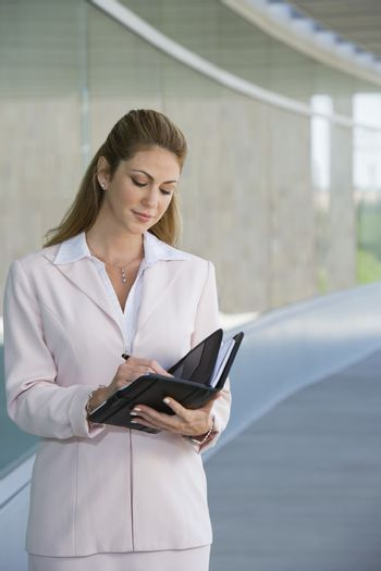 Young businesswoman writing in planner