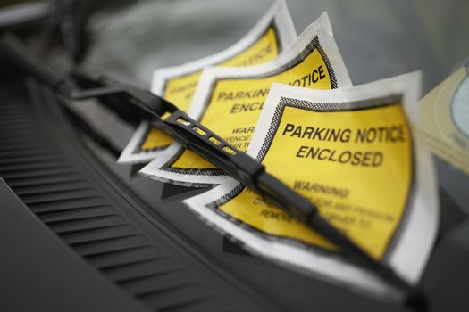 Closeup of parking tickets under windshield wiper of a car